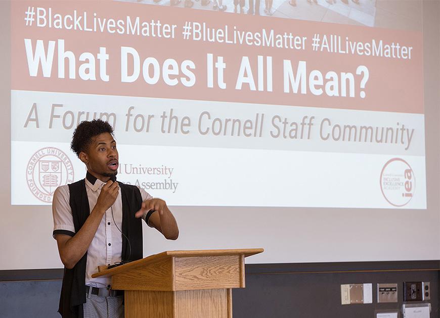 A man speaking in front of a large screen that says #BlackLivesMatter #Blue LivesMatter #AllLivesMatter, What Does It All Mean?