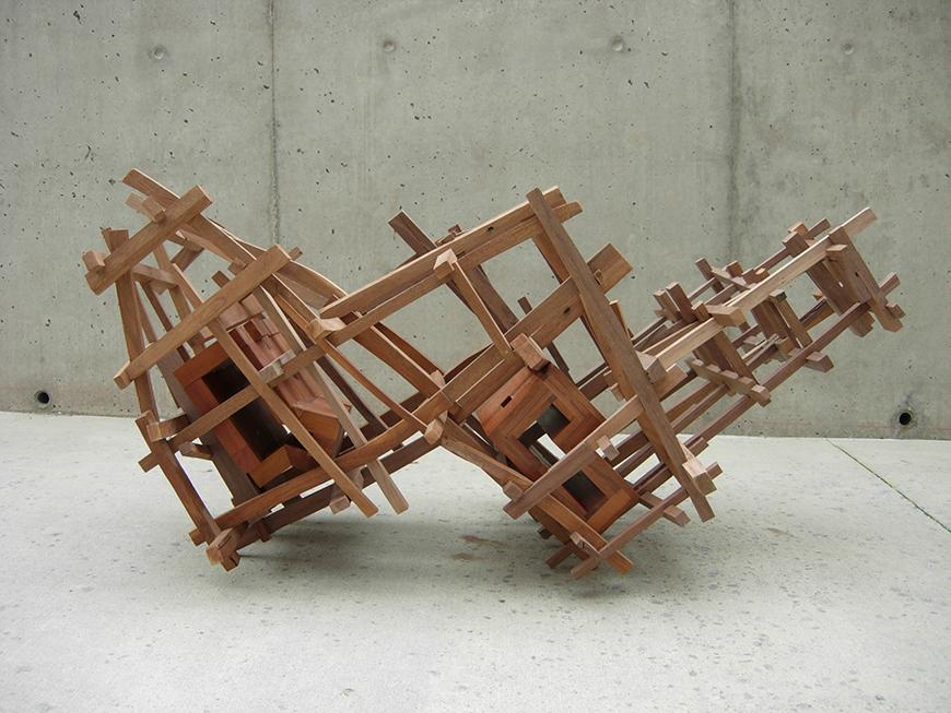 Abstract sculpture piece with wooden pieces attached to one another in a checkered W formation.