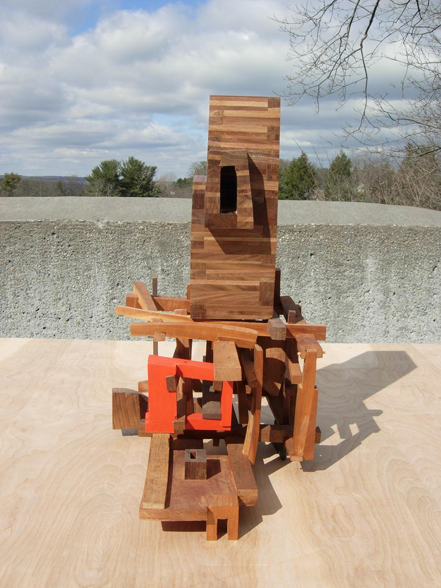 Abstract sculpture piece of wooden pieces attached together photographed outside.