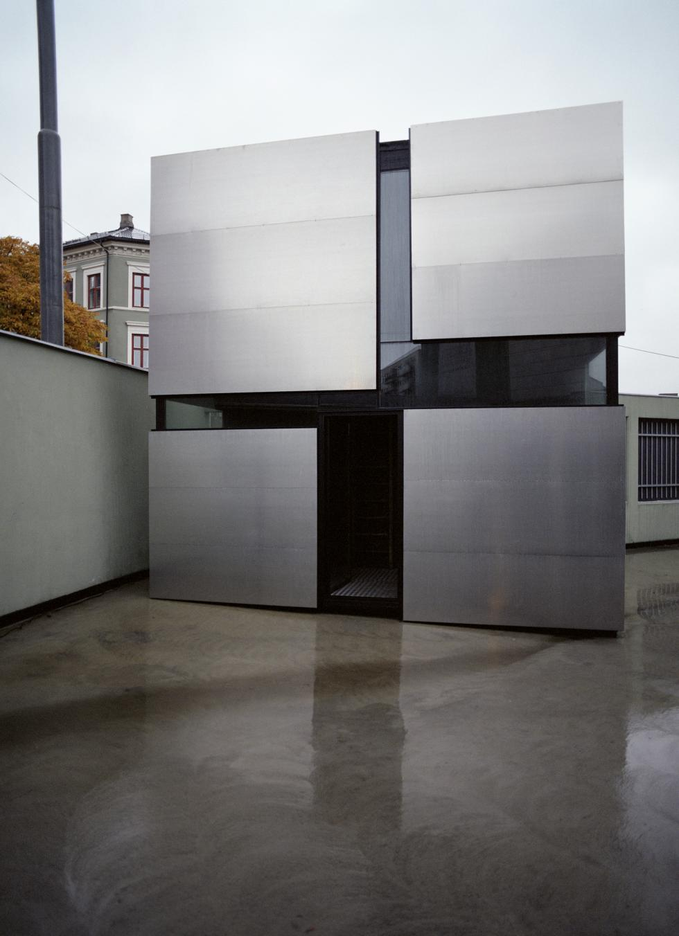 Silver paneled facade with 4 squares separated by black glass.