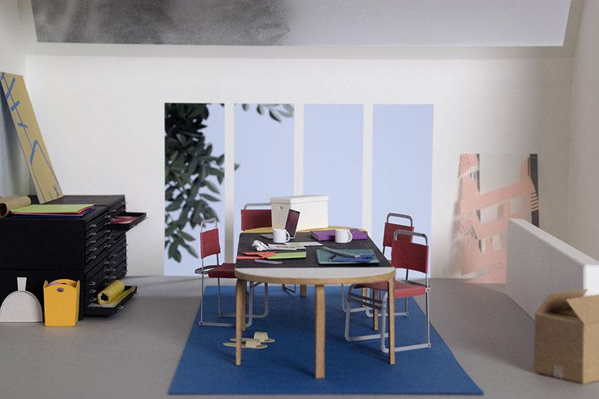 A small replica of an interior studio space constructed from paper, and occupied by a table and four red chairs at its center.