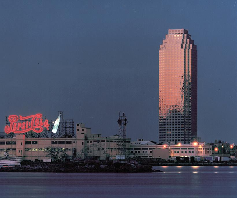High-rise building and lighted Pepsi Cola sign at dusk