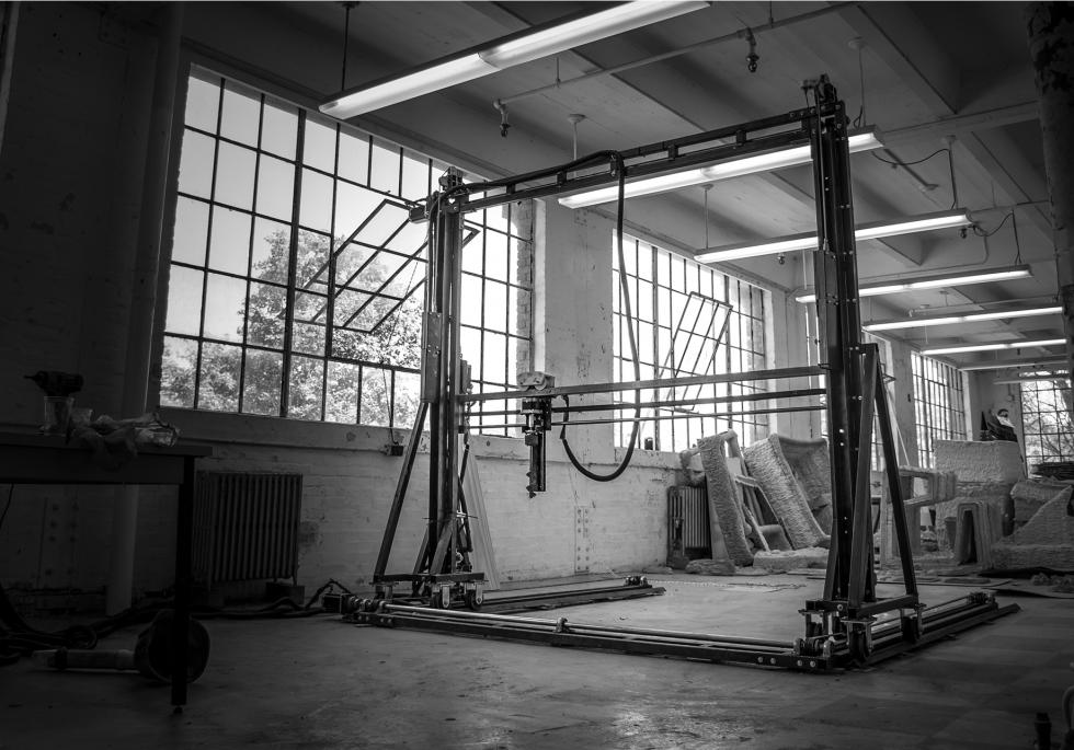 black and white photo of an upright machine sitting in a building with large square windows