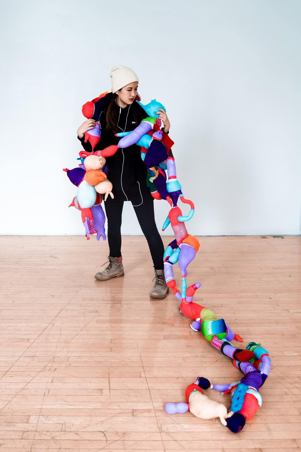 Colorful abstract shapes sewn together, draped across a woman wearing black clothes and gray boots.