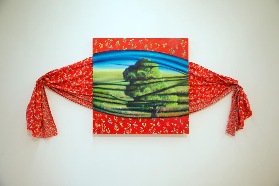 Red fabric with small flowers printed across it tied at the ends with a painting of a tree in the middle on canvas made to look like fabric.