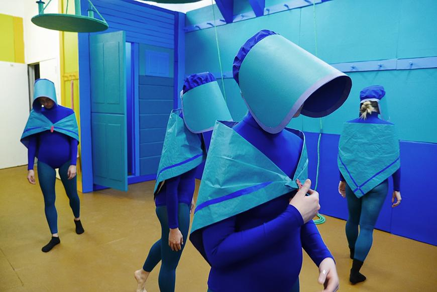4 women dressed in blue leotards, small blue capes, and blue cone-shaped bonnets walk inside a blue gallery space
