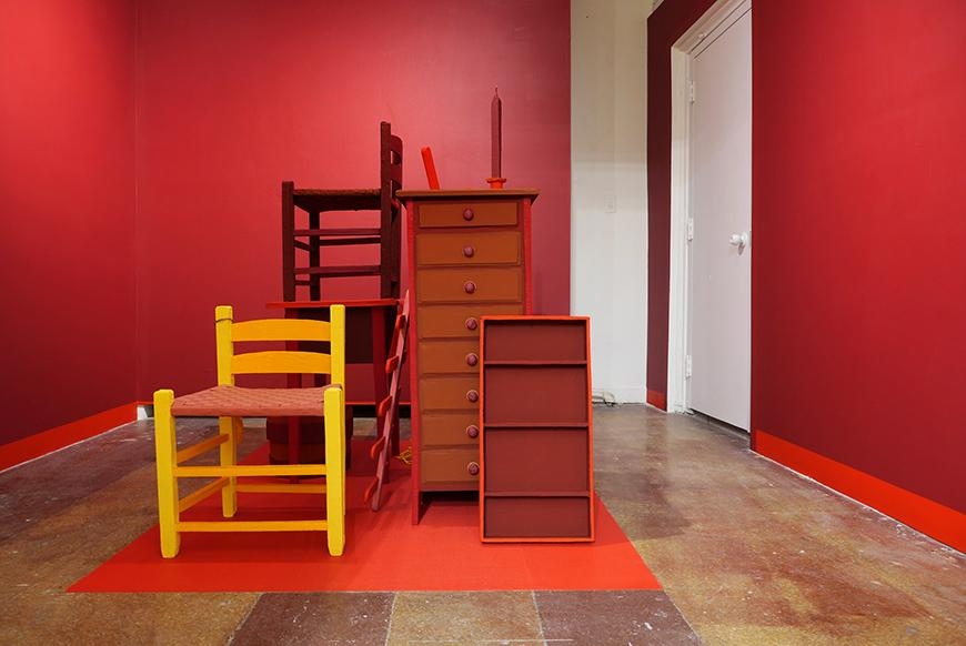 Red and orange wooden chairs, bookcases, a candle, and chest of drawers stacked on a rectangle painted red, with red painted walls and a white door