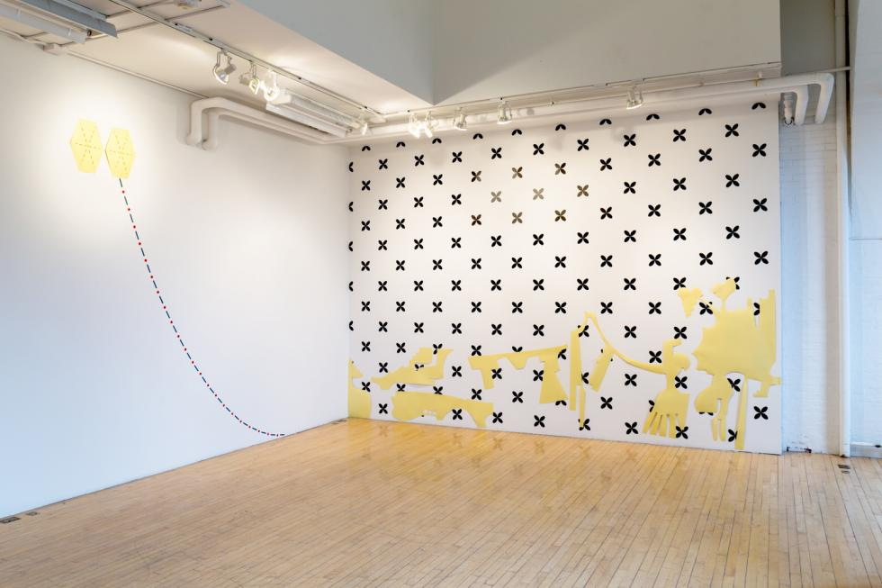 black star shapes against a white wall with yellow abstract shapes draped across