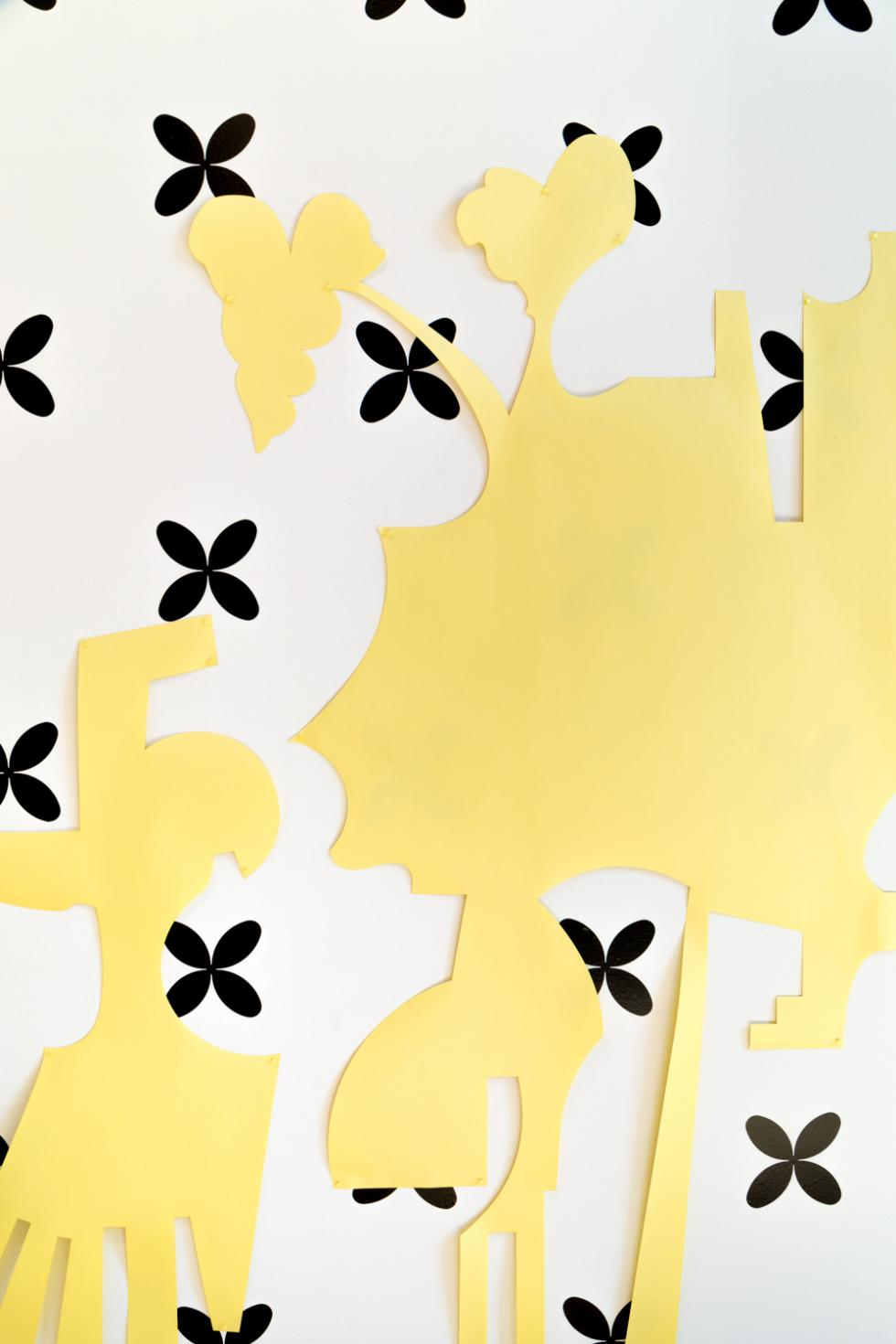 detail of black star shapes against a white wall with yellow abstract shapes draped across