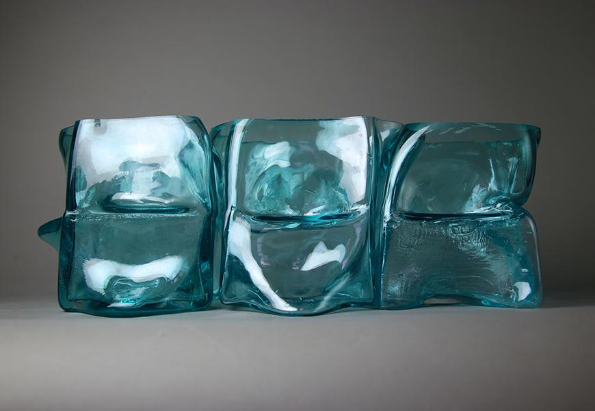 A blue, glass object consisting of a series of abstract squares molded together.