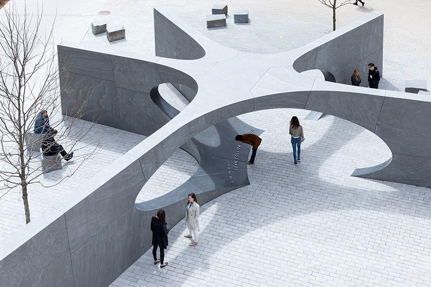 five pointed star-shaped sculpture with people walking around and underneath the central arch