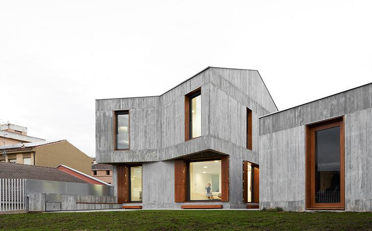 contemporary two story concrete residence with an angled buttress and large windows