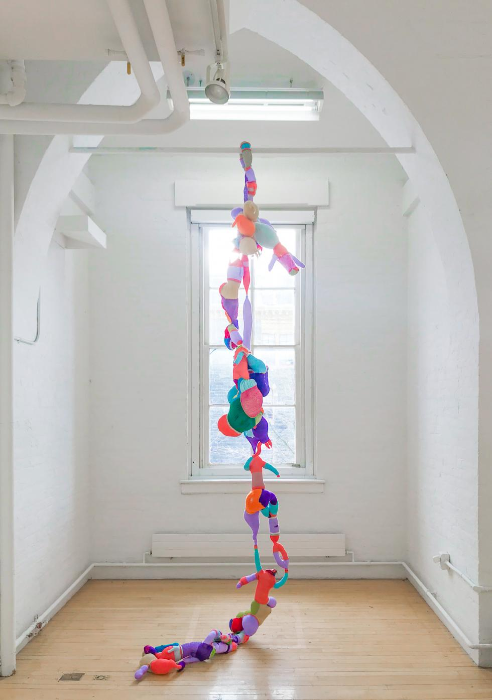 Colorful fabric shapes sewn together and hanging from a horizontal white pole set in front of a window.