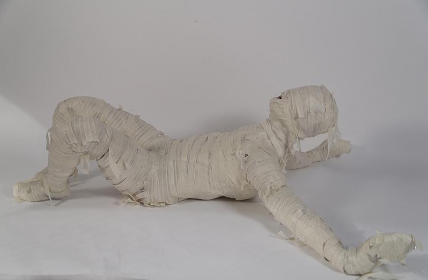 White background with a sculpture of a person lying on the ground wrapped in masking tape.