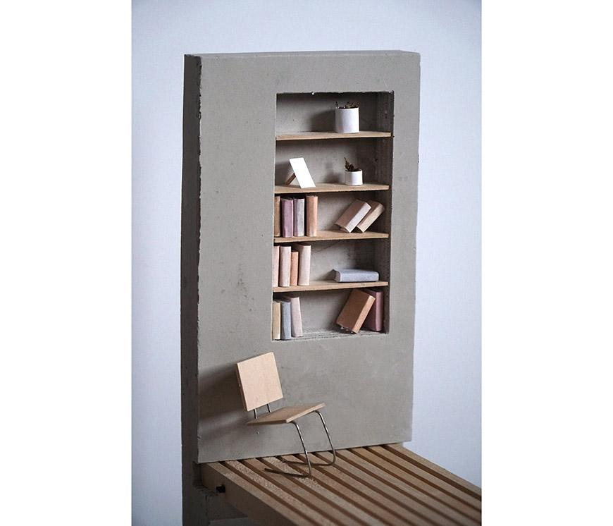 Small model of a bookcase and chair.