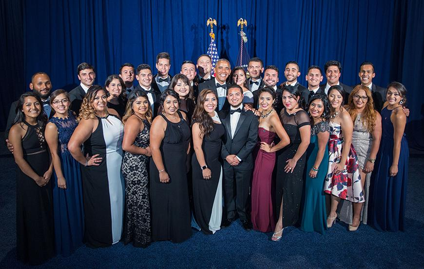 Men and women in formal wear posing for a photo with President Obama in front of a curtain and flags
