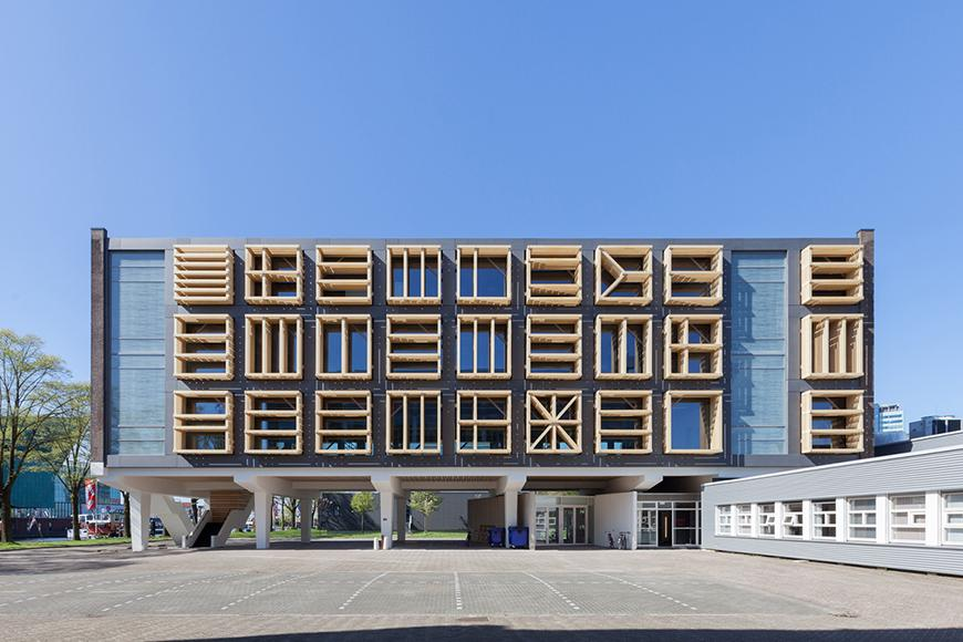 A building whose windows and facade are covered by a series of geometric screens.