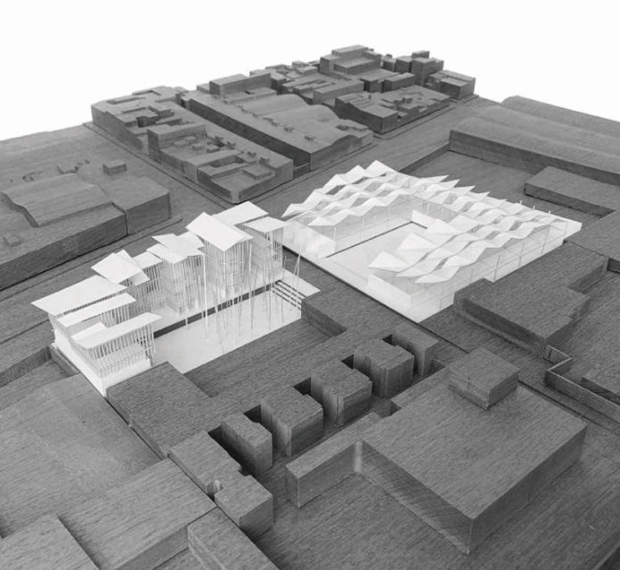 Site model made out of wood and paper showing overall building taking over two plots of land.