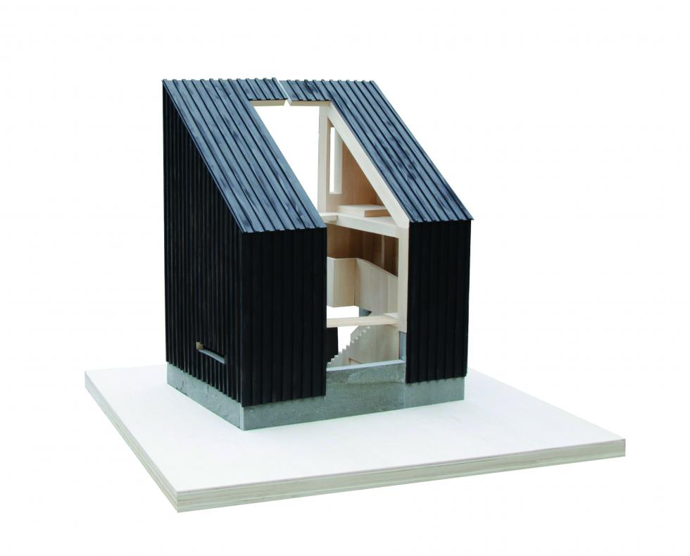 Half of model showing the exterior made out of black wood shingles with an opening in the middle.