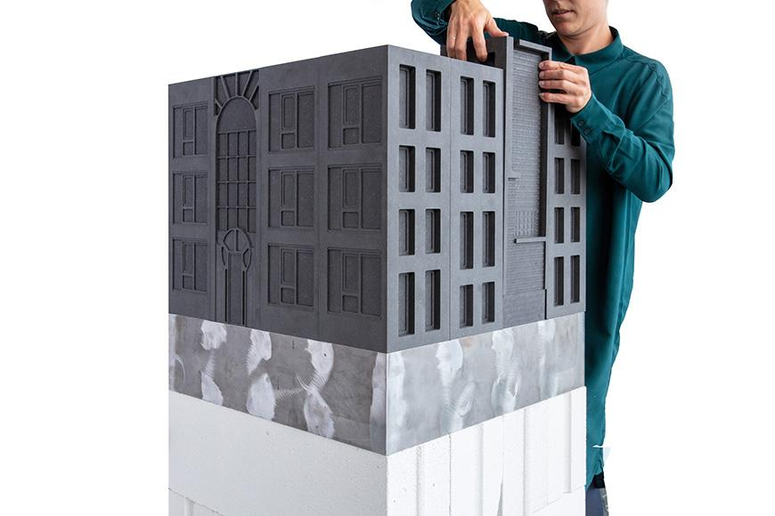 A model of a building which has been rendered entirely in grey material, and placed within a gallery space. The model is elevated and placed on a white and grey podium.