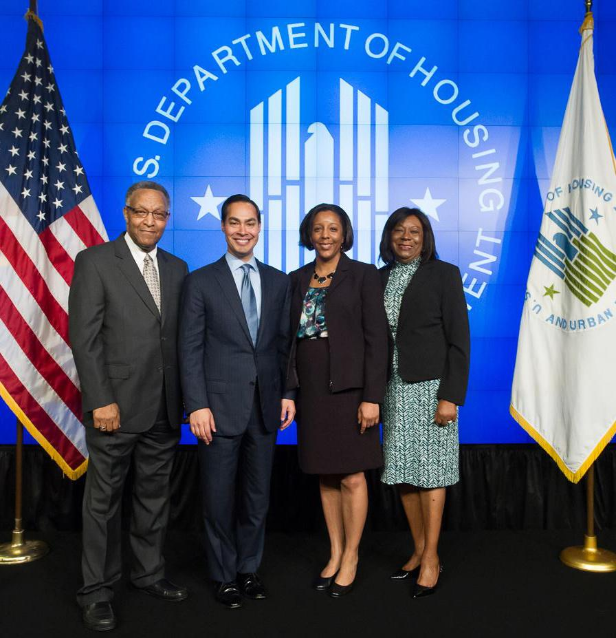 Two men and two women posed with the American flag and the HUD seal