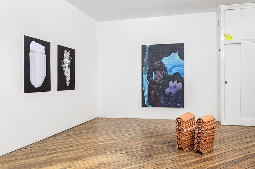 Two black and white images on one wall, an abstract blue, brown and purple painting on another wall, and two stacks of ceramic tiles on a wooden floor.