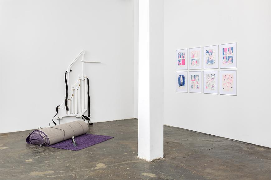 Purple rolled up carpet on a cement floor next to a white railing on the wall with black fabric hanging down next to eight white framed prints depicting cartoon scenes in pink and blue.