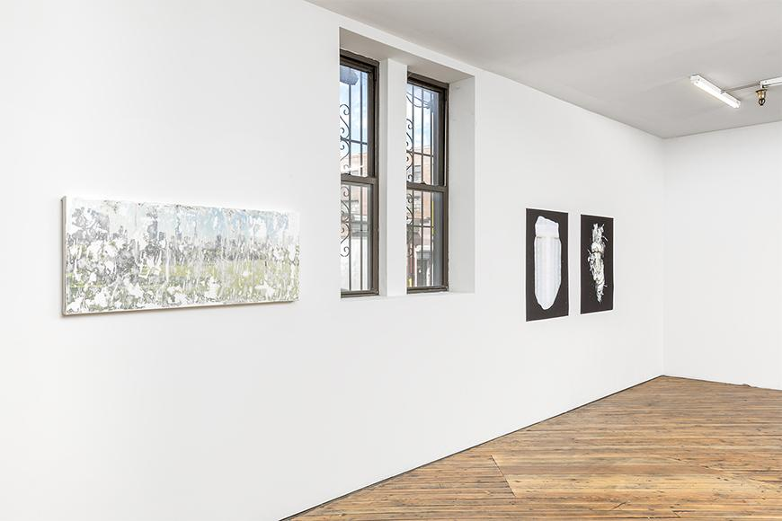 White wall with wooden floors featuring a faded green, grey and blue abstract image, a window, and two black and white images.