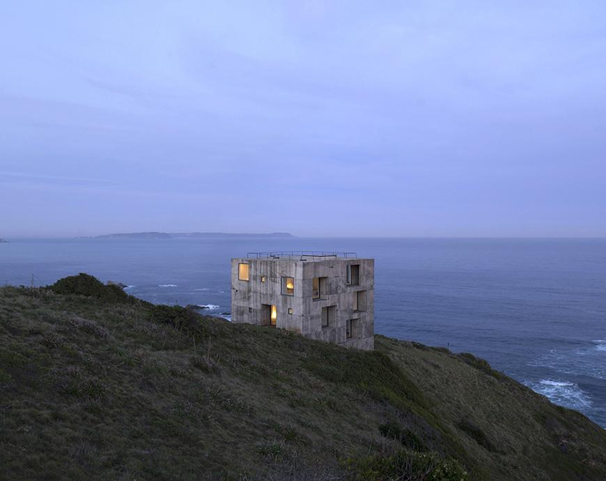 a concrete building on a seaside cliff top