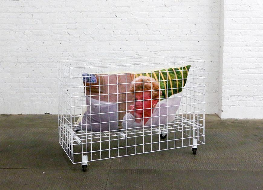 A pillow featuring Angela Lansbury is in a white cage with rolling wheels on the bottom on a concrete floor with a white brick background.