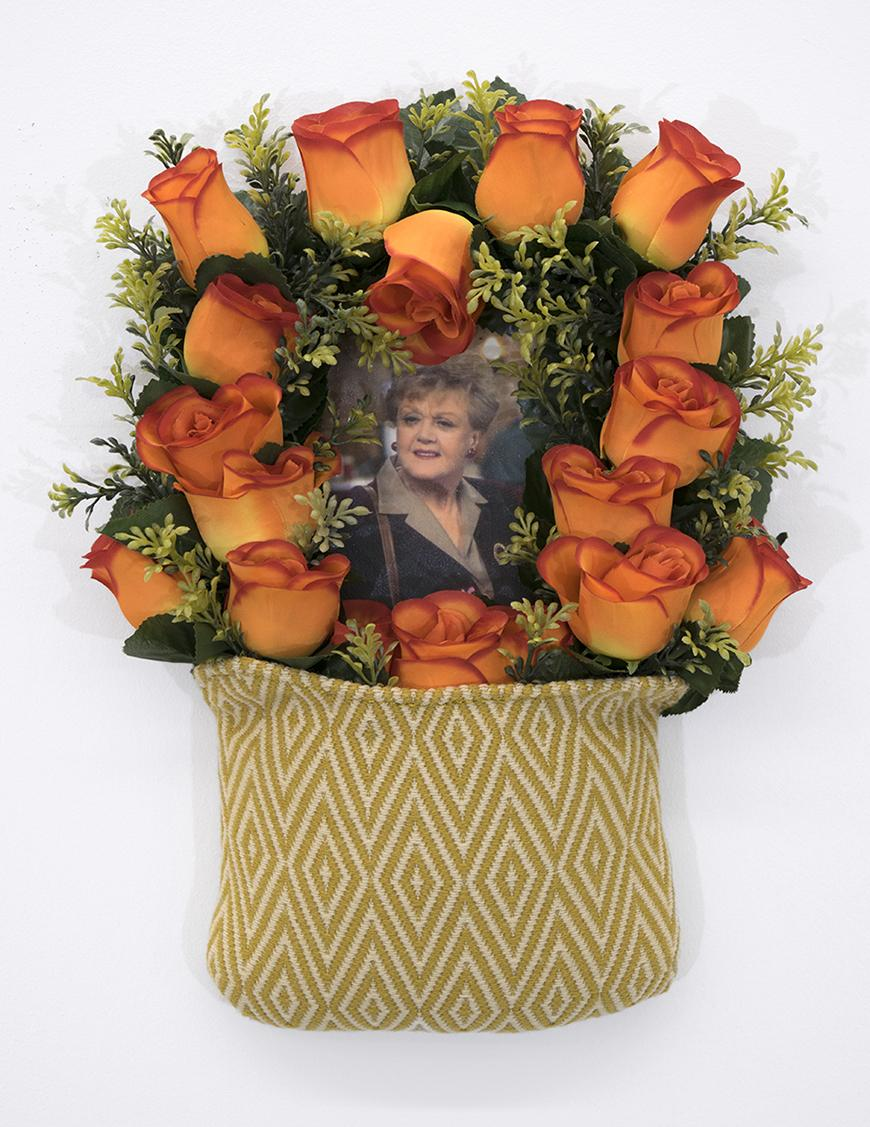 Diamond pattern bag holding orange roses with greenery featuring a picture of Angela Lansbury.