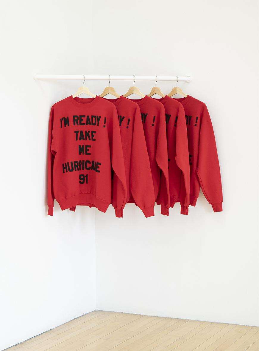 Five red sweatshirts hanging on a white rod with the words