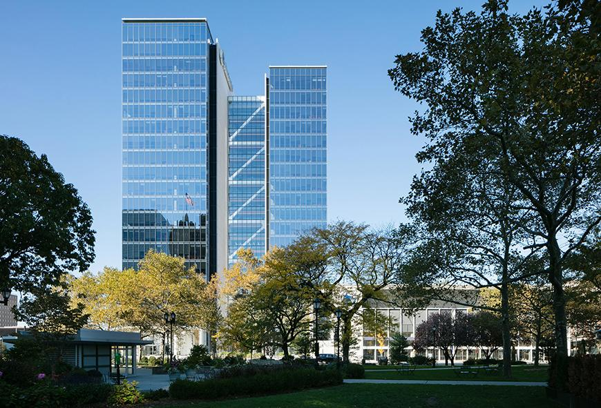 Three interlocked multi-story office towers faced with glass windows reflecting blue sky set in a leafy office capus.