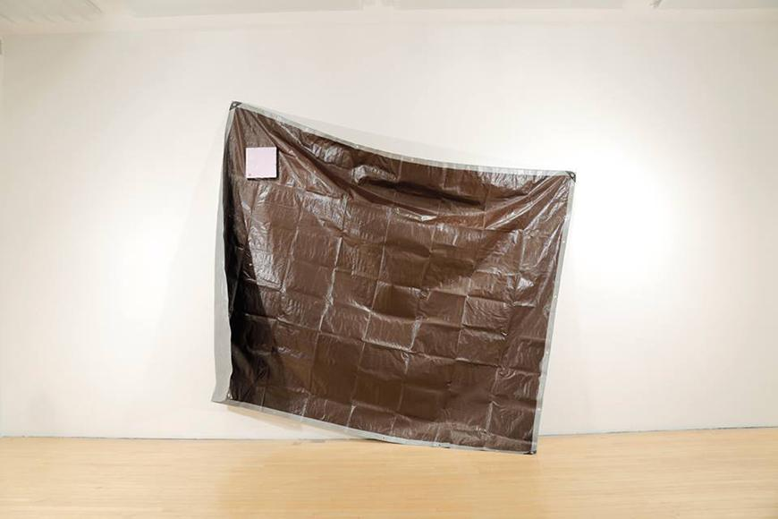 A dark tarp hung on the wall at an angle with a painted square in the upper left hand corner.