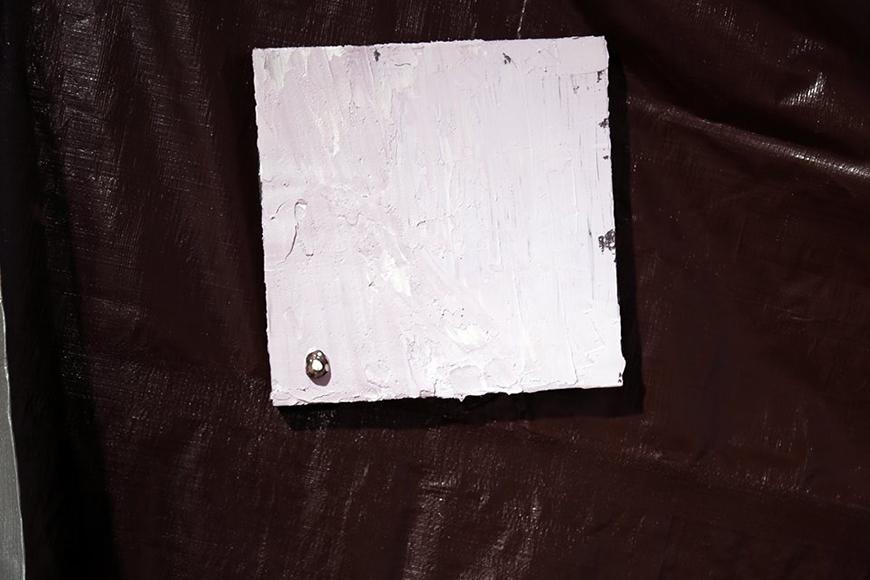 Light painted square placed over a dark colored tarp with a stone attached to the bottom left of the square.