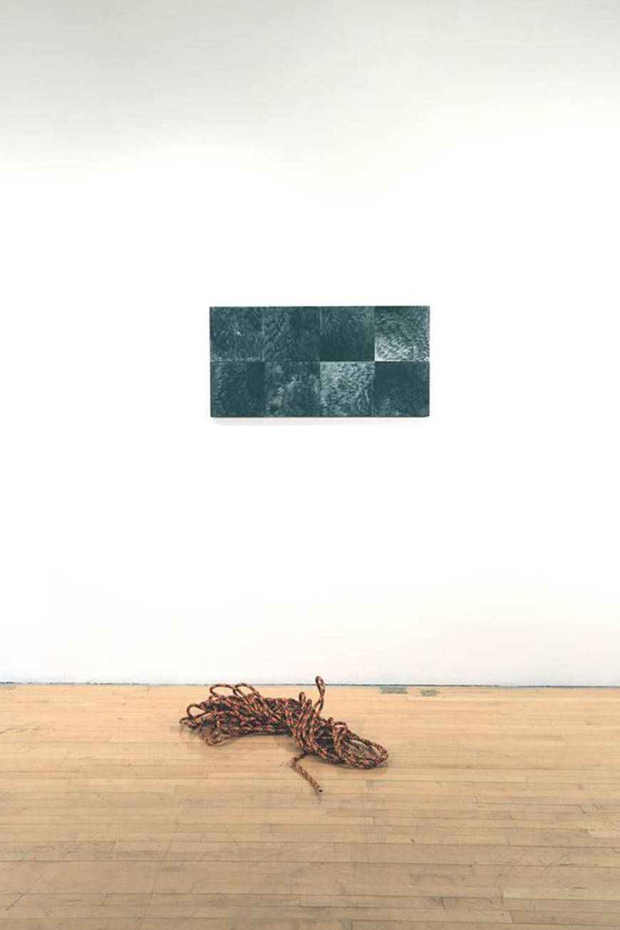 Coiled rope on the floor with a rectangular abstract painting above it.