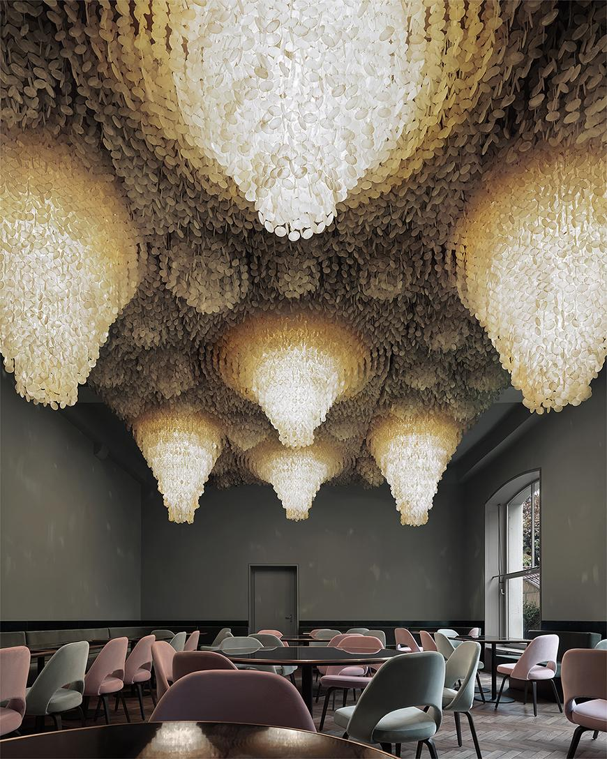 Decorative and illuminated drop down ceiling, situated above a modern, open room populated by light pink and green chairs.