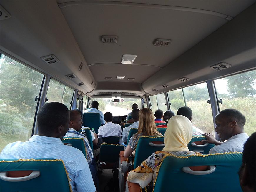 People riding a bus, taken from the back of the bus