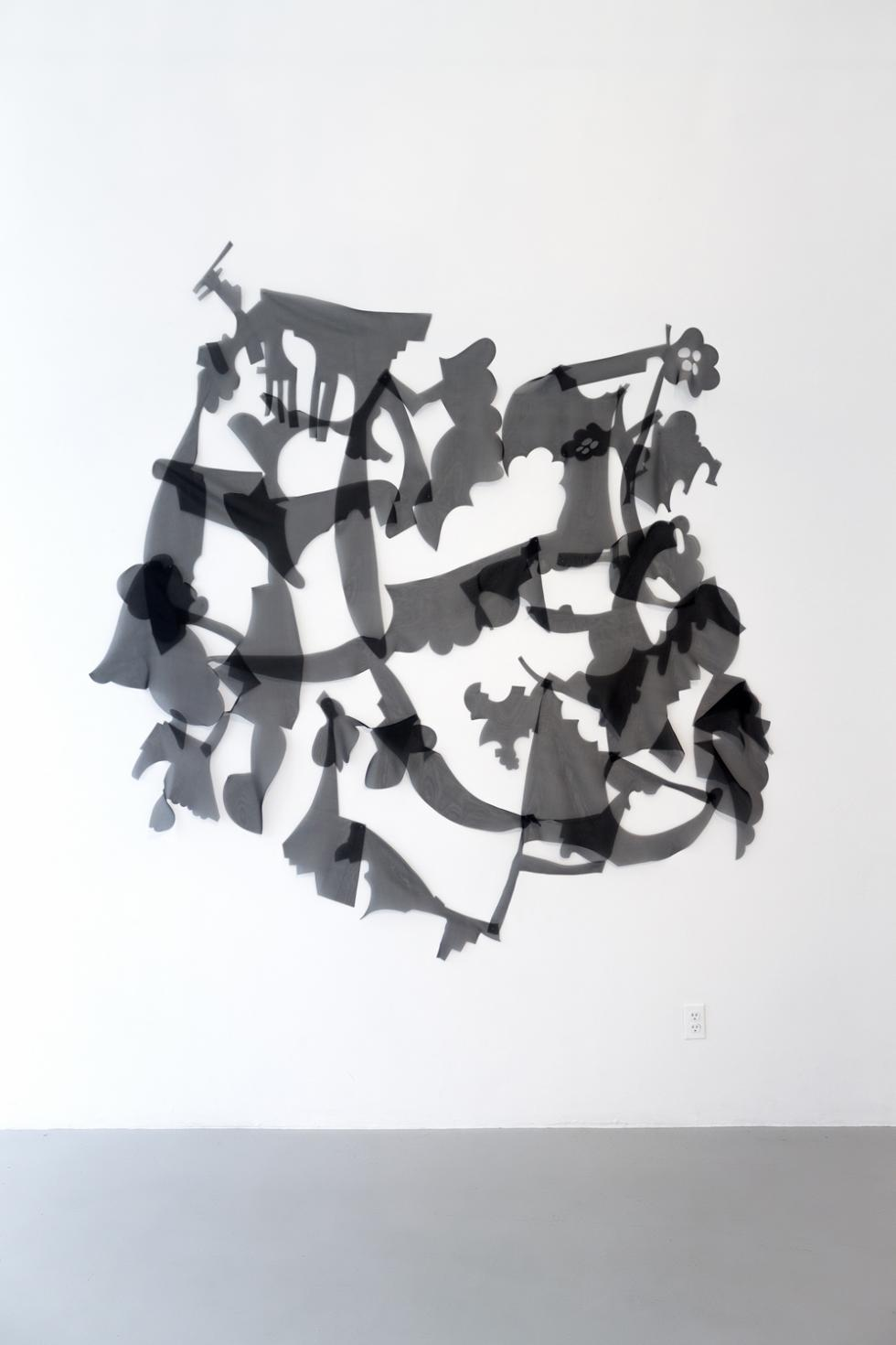 black transparent abstract shapes against a white wall