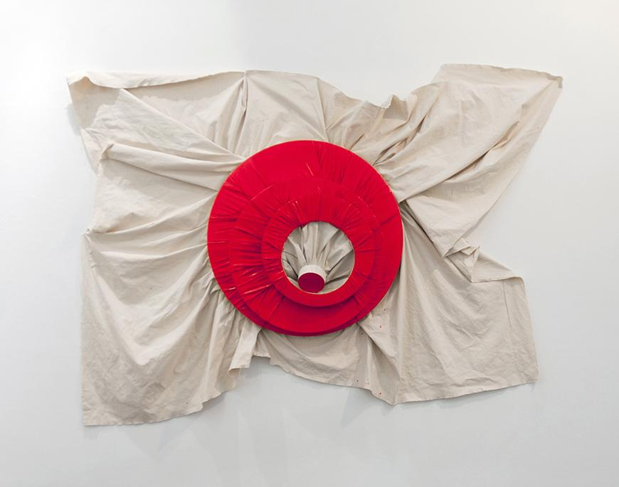 Red colored circular fabric with a hole cut in the middle on top of a white sheet pinned to the wall.