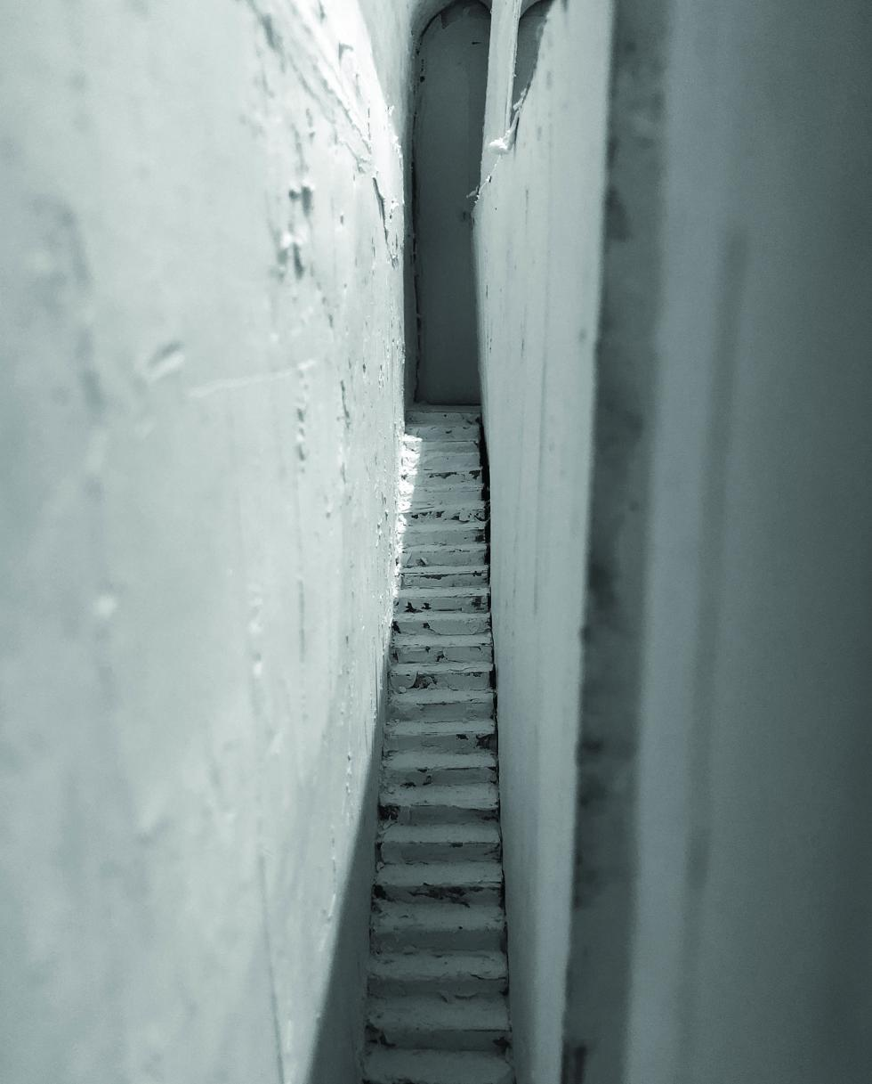 Gray stairs inside a narrow alley.