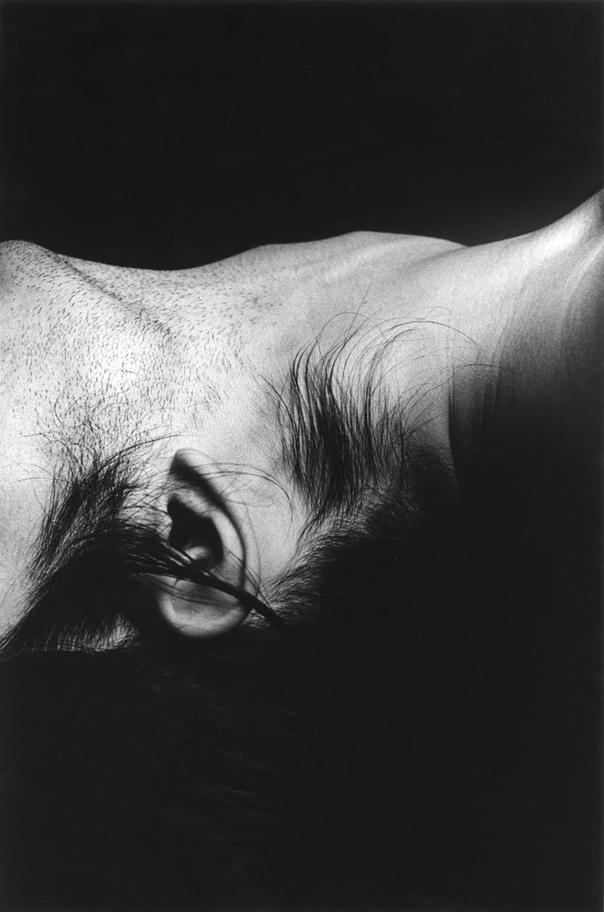 Black and white photograph of a person's neck and ear.