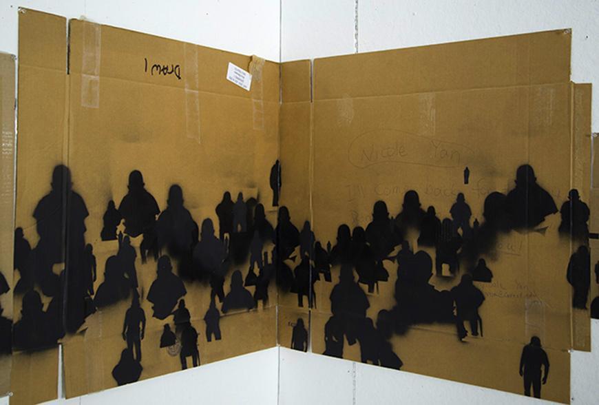 Black spray painted figures on cardboard.