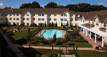 A three-story apartment complex with a pool