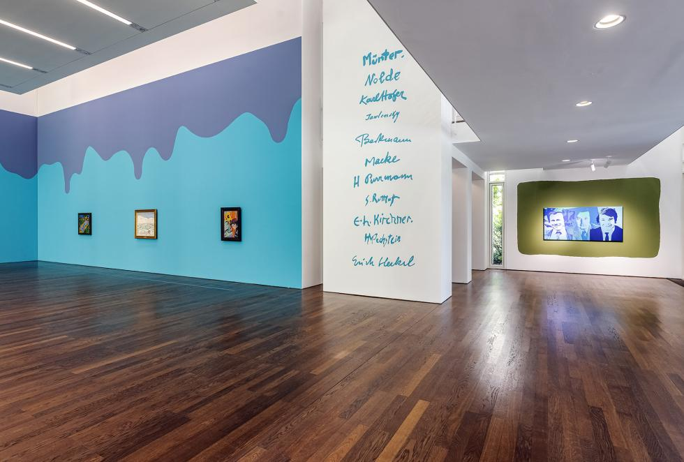 Large painted walls with smaller paintings hung next to a white wall with blue words on dark wooden floors.