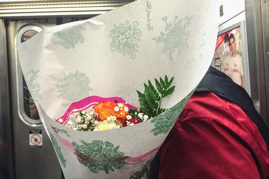 Photograph of someone on a subway holding a bouquet of flowers blocking their face.