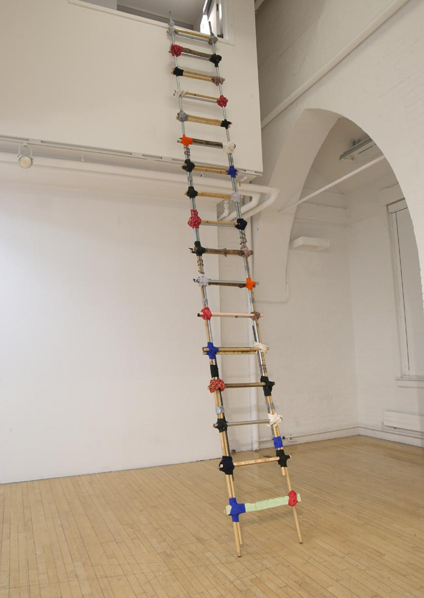 Multi-colored ladder made from various materials propped up against a wall.