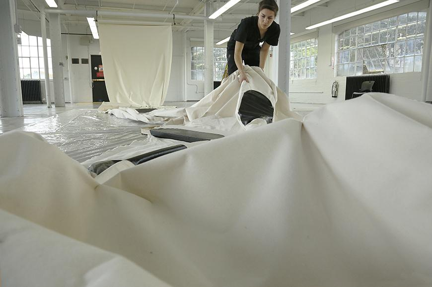 Artist laying out long pieces of white fabric on the floor.