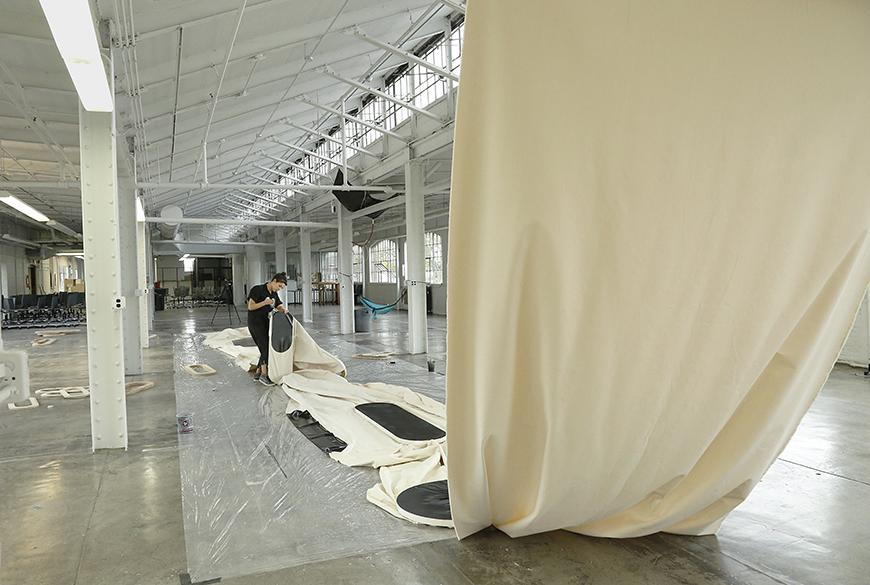 Artist laying down white cloth with black oblong shapes painted on it on the floor.