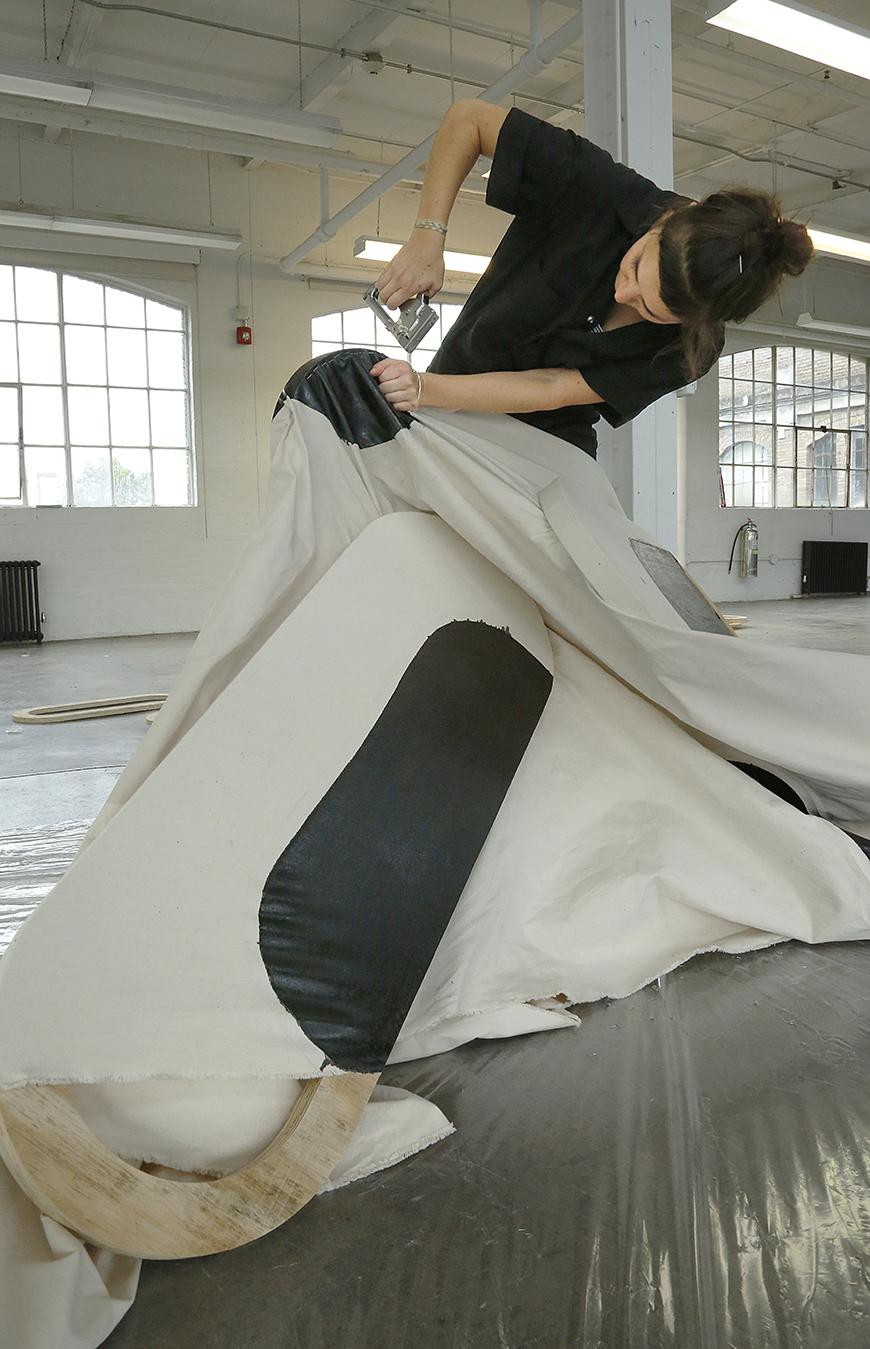 Artist stapling white cloth with black shapes painted on it to a wooden oblong shape.